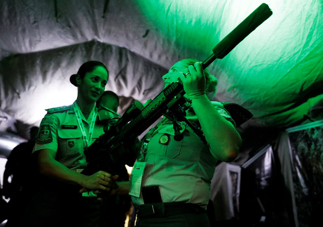Military officers look at an AR-10 sniper rifle at LAAD, the biggest military industry expo in Latin America in Sao Paulo, Brazil April 10, 2018. (Photo by Nacho Doce/Reuters)