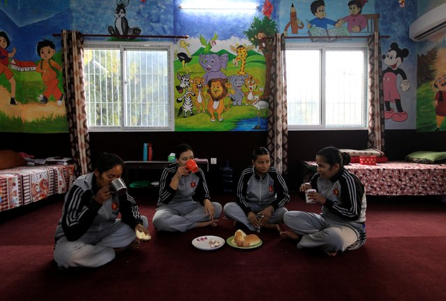 """Krishna Kumari, a 37-year-old sergeant, along with Rachana, a 25-year-old corporal, Leela, a 25-year-old private, and Rashmi, a 25-year-old corporal, eat breakfast before being discharged from quarantine on the premises of an army barracks in Kathmandu, Nepal, November 21, 2020. """"It is my duty to remove the dead bodies and I am proud of what I am doing"""", said Krishna Kumari. The 37-year-old sergeant added: """"The work is physically demanding ... and we have proved that women are capable of doing difficult tasks during the pandemic"""". (Photo by Navesh Chitrakar/Reuters)"""