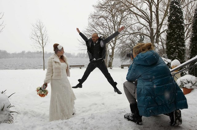 Cornelia and Nikolay Reithmeier celebrate their wedding in the snow while a photographer, Nadine, takes pictures of them at a lake in Olching, southern Germany, December 30, 2014. (Photo by Michaela Rehle/Reuters)
