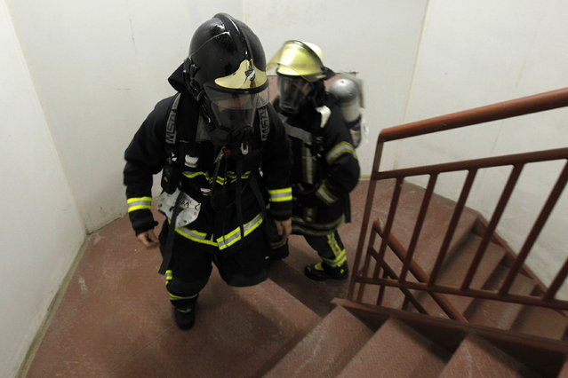 """Firefighters climbs through the stairs of the Costanera Centre Tower in Santiago as part of the """"Race for Life"""" aimed at encouraging organ donation in Chile, in Santiago, on October 16, 2016. (Photo by Claudio Reyes/AFP Photo)"""