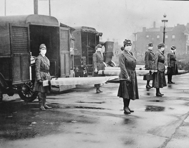 In this October 1918 photo made available by the Library of Congress, St. Louis Red Cross Motor Corps personnel wear masks as they hold stretchers next to ambulances in preparation for victims of the influenza epidemic. A century after one of history's most catastrophic disease outbreaks, scientists are rethinking how to guard against another super-flu like the 1918 influenza that slaughtered tens of millions as it swept the globe in mere months. (Photo by Library of Congress via AP Photo)