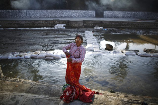 A devotee gets dressed after taking a holy bath in River Saali in Sankhu on the first day of Swasthani Brata Katha festival in Kathmandu January 5, 2015. (Photo by Navesh Chitrakar/Reuters)