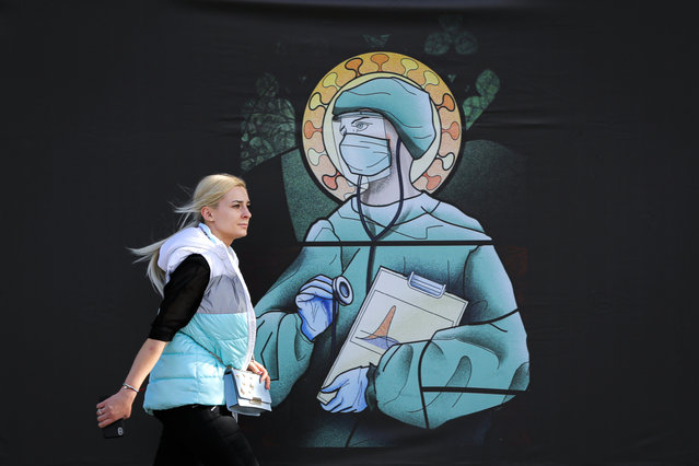 """A woman walks by a depiction of a medical staff wearing protective equipment, executed in the style of orthodox icons, in Bucharest, Romania, Wednesday, April 29, 2020. The artwork, among others depicting medical staff in the manner of religious icons, created by designer Wanda Hutira, is part of a campaign called Thank You Doctors, meant to raise awareness to the work of medical staff fighting the COVID-19 pandemic. Following public pressure by Romania's influential Orthodox church the artworks, described as """"blasphemous"""" will be removed from all locations in the Romanian capital, according to the agency behind the project. (Photo by Vadim Ghirda/AP Photo)"""