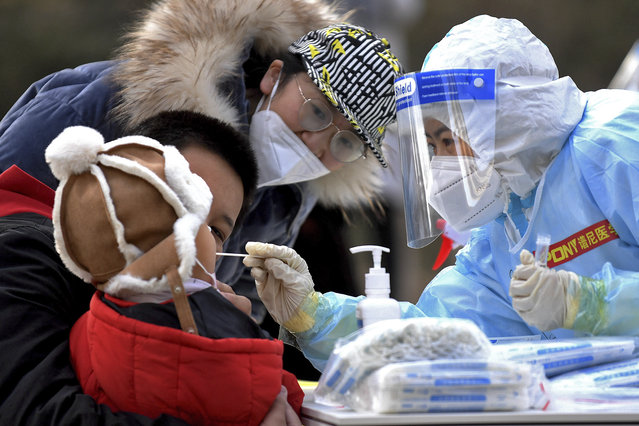 In this photo released by Xinhua News Agency, a medical staff in a protective suit takes a swab from a child near a residential area in Shijiazhuang in northern China's Hebei Province on Sunday, January 10, 2021. Chinese health authorities say scores more people have tested positive for coronavirus in Hebei province bordering on the capital Beijing. The outbreak focused on the Hebei cities of Shijiazhuang and Xingtai is one of China's most serious in recent months and comes amid measures to curb the further spread during next month's Lunar New Year holiday. (Photo by Wang Xiao/Xinhua via AP Photo)
