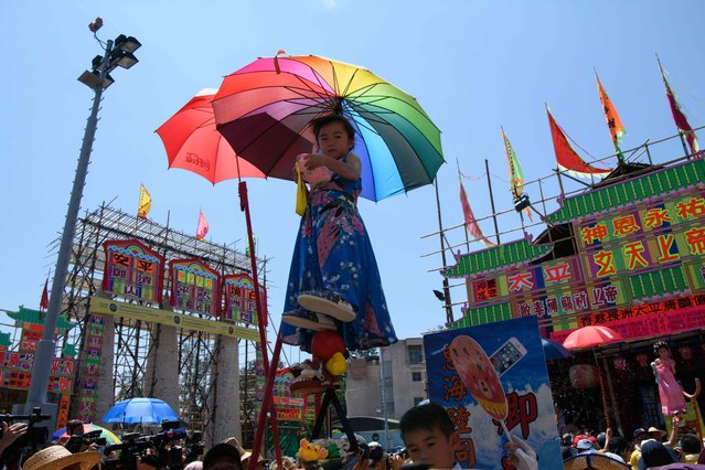 Hazel Kwok (C), 4 years old, stands on a float while portraying her character of former lawmaker Emily Lau during the annual Cheung Chau bun festival parade in Hong Kong on May 22, 2018. (Photo by Anthony Wallace/AFP Photo)