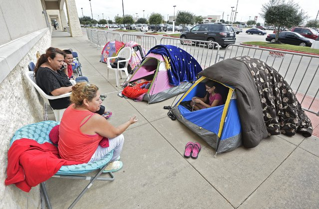 Members of the Vazquez family sit outside their tents along with other people while camping out in tents outside a Best Buy store two days ahead Black Friday shopping in a suburb of Houston, Texas in Rosenberg, Texas, USA, 25 November 2015. Retailers in the United States have looked to the Friday after Thanksgiving, known as Black Friday, as an opportunity to make a large amount of holiday sales, though the tradition in recent years has been pushed into Thanksgiving evening. (Photo by Larry W. Smith/EPA)