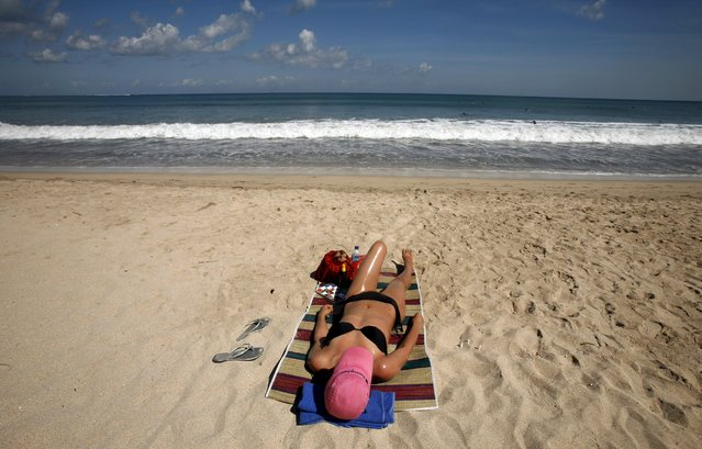 A tourist sunbathes at Kuta beach on Indonesia's resort island of Bali in this June 5, 2008 file photo. Indonesia is expected to release tourist arrival numbers for October this week. (Photo by Murdani Usman/Reuters)