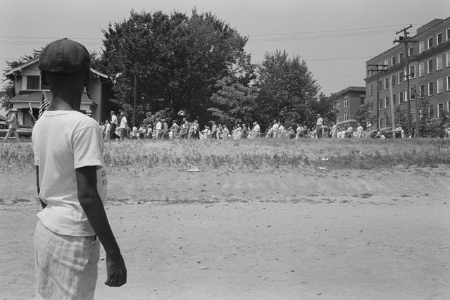 "A young boy watching a group of people, some carrying American flags, march past to protest the admission of the ""Little Rock Nine"" to Central High School in Little Rock, Arkansas, August 20, 1959. (Photo by Reuters/Library of Congress)"