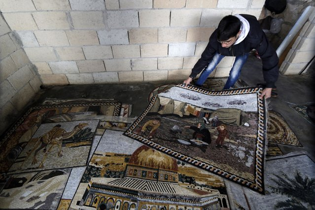 A man holds a mosaic artwork depicting life at a refugee camp, over another depicting the Dome of The Rock at a workshop in Kafranbel town in the Idlib governorate January 17, 2015. (Photo by Khalil Ashawi/Reuters)