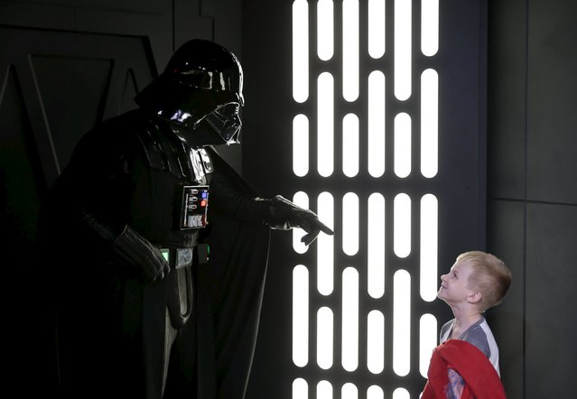 A young guest interacts with the character Darth Vader during the Star Wars Launch Bay grand opening at Disney's Hollywood Studios in Orlando, Florida December 4, 2015. (Photo by Scott Audette/Reuters)