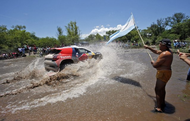 An Argentinian supporter holds an Argentinian flag as he cheers on Peugeot driver Cyril Despres of France crossing a river during the 11th stage of the Dakar Rally 2015 from Cachi to Termas de Rio Hondo January 15, 2015. (Photo by Jean-Paul Pelissier/Reuters)