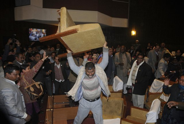 A constitution assembly member of an opposition party throws a chair during a meeting inside the Constitution Assembly building in Kathmandu January 20, 2015. The new assembly was elected to write a constitution after the abolition of the 240-year-old feudal monarchy that the Maoists fought against. (Photo by Bikash Dware/Reuters)