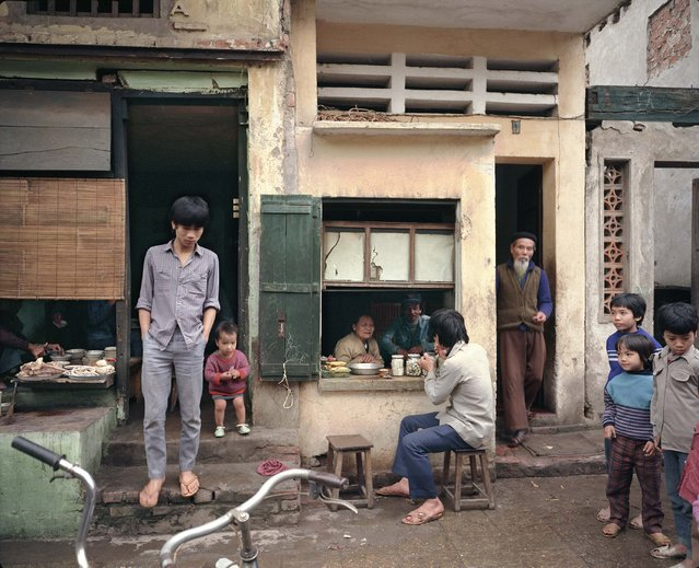 "Documentary photographer William E. Crawford was one of the first Western photographers to gain access to North Vietnam after the war ended. He has photographed the capital, Hanoi, at regular intervals since 1985, concentrating on the colonial and indigenous architecture, urban details, landscapes and intimate portraits of people in their home settings, street scenes and the city's surrounding countryside. Crawford is the only known Western or Vietnamese photographer to approach Hanoi as a study over time. In the years before the tourist boom, he was often the only American in the North. Crawford's early photographs reveal a city in extreme disrepair, but with enough colonial and precolonial detail remaining to give a sense of what the city had looked like in better times. Here: 72 Mã Mây (Rattan Street), 1988. (Photo by  William E. Crawford from the book ""Hanoi Streets 1985-2015: In the Years of Forgetting"")"