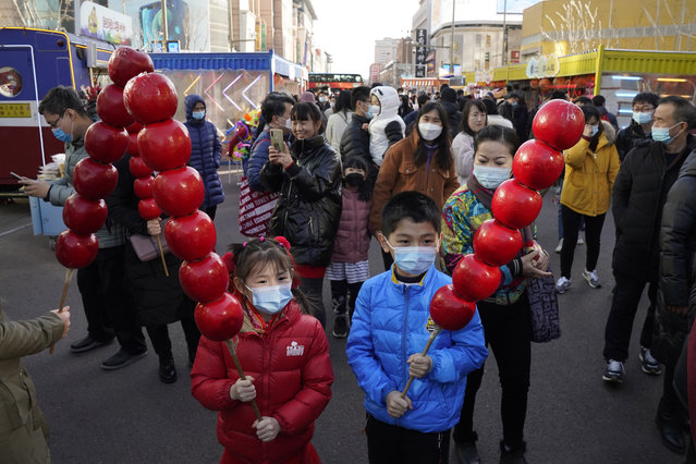 Young children wearing masks to protect from the coronavirus pose for photos with giant replica of candy haw, a popular Beijing snack, at a street stall near Wangfujing on the fourth day of the Lunar Chinese New Year in Beijing on Monday, February 15, 2021. (Photo by Ng Han Guan/AP Photo)