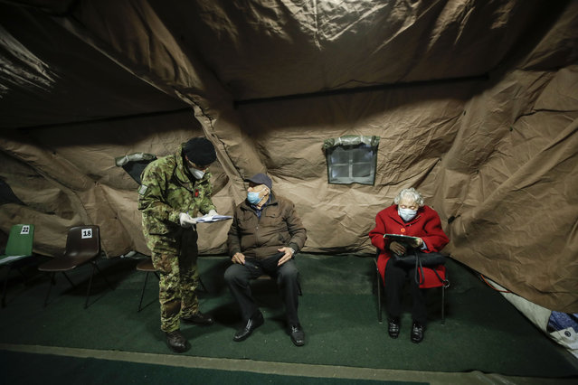 Over eighty-year-olds wait to be administered a dose of the Pfizer/BioNTech vaccine, in a tent set up at the Baggio military hospital in Milan, Italy, Thursday, February 18, 2021. (Photo by Luca Bruno/AP Photo)