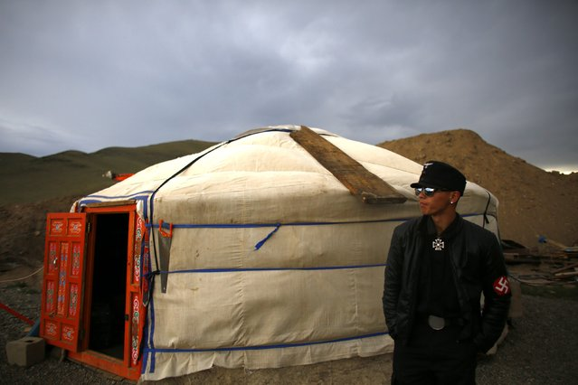 A member of the Mongolian neo-Nazi group Tsagaan Khass stands next to a 'ger', a traditional Mongolian tent, at a quarry, where they questioned a worker, southwest of Ulan Bator June 23, 2013. (Photo by Carlos Barria/Reuters)
