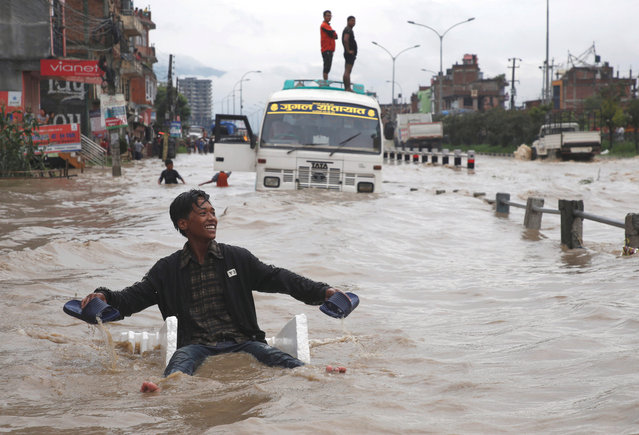 A boy smiles as he uses an improvised raft to maneuver through the floodwater after incessant rainfall in Bhaktapur, Nepal on July 12, 2018. (Photo by Navesh Chitrakar/Reuters)