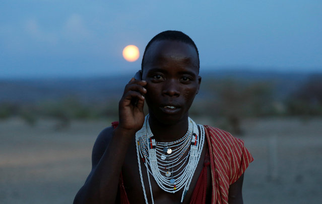 A Maasai tribesman talks on his phone as they gather to witness the rise of the supermoon in Oloika village in Shompole, Magadi near the Kenya-Tanzanian border, November 14, 2016. (Photo by Thomas Mukoya/Reuters)