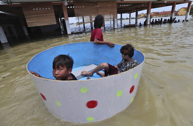 Indonesian boys sit inside a tub during a flood in Bekasi, Indonesia, Monday, February 22, 2021. (Photo by Achmad Ibrahim/AP Photo)