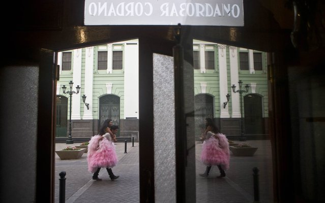 """Daysi Villavicencio rides on the back of a photographer's assistant to keep her gown from getting dirty as they're reflected in a mirror at the iconic Cordano Bar in Lima, Peru, Thursday, January 22, 2015. Villavicencio is celebrating her 15th birthday and had a series of pictures made in her formal """"quinceañera"""" gown. (Photo by Esteban Felix/AP Photo)"""