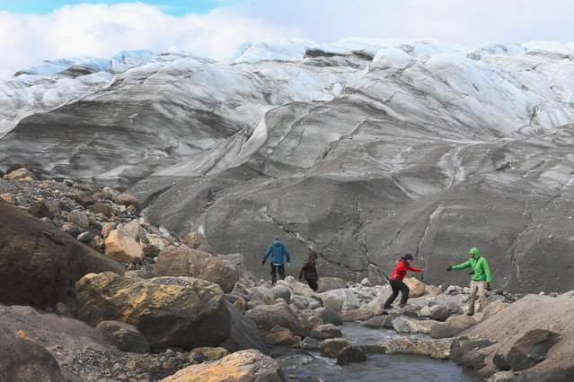 Ellen E. Martin, (L) Department of Geological Sciences at the University of Florida, crosses in front of a glacier as she works with her team to analyze the water chemistry coming out of the glacial environment and using that to understand how the melt is effecting the sea waters on July 10, 2013 in Kangerlussuaq, Greenland. (Photo by Joe Raedle/Getty Images via The Atlantic)