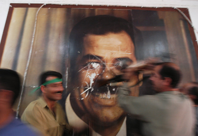 Kurdish Peshmerga soldiers deface a poster of former Iraqi leader Saddam Hussain's poster in the Kirkuk Governate building in Kirkuk hours after it fell from Iraq Central Government rule, April 10, 2003.  (Photo by Lynsey Addario/Corbis)