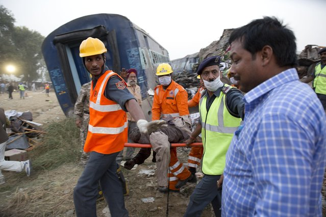 A relative, right, breaks down as rescuers carry the body of a victim after 14 coaches of an overnight passenger train rolled off the track near Pukhrayan village Kanpur Dehat district, Uttar Pradesh state, India, Sunday, November 20, 2016. Dozens were killed and dozens more were injured in the accident. (Photo by Rajesh Kumar Singh/AP Photo)