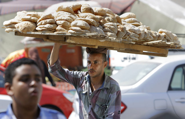 An Egyptian vendor carries bread downtown Cairo, Egypt, Monday, August 5, 2013. Egypt's central bank reported Monday that foreign reserves reached $18.8 billion, their highest level in almost two years, but economists caution the boost is a reflection of aid from oil-rich Arab Gulf nations and not the result of an improved economy. The July reserve figures, which were released on the central bank's website, represent a nearly $4 billion jump from $14.9 billion at the end of June. (Photo by Amr Nabil/AP Photo)