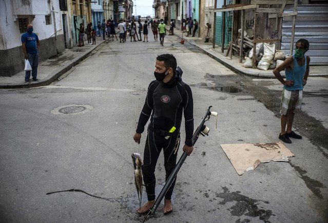 Wearing a protective face mask as a precaution against the spread of the new coronavirus, diver Yuniel Gonzalez walks home with his catch of the day, in Havana, Cuba, Tuesday, October 27, 2020. Cuba relaxed COVID-19 restrictions earlier this month in hopes of boosting its economy, allowing shops and government offices to reopen and welcoming locals and tourists at airports across the island. (Photo by Ramon Espinosa/AP Photo)