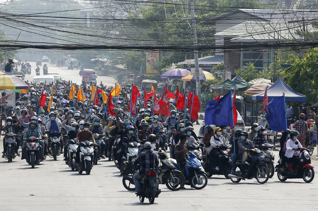 "Protesters carry flags as they drive their motorcycles during an anti-coup protest in Mandalay, Myanmar on Thursday March 25, 2021. Protesters against last month's military takeover in Myanmar returned to the streets in large numbers Thursday, a day after staging a ""silence strike"" in which people were urged to stay home and businesses to close for the day. (Photo by AP Photo/Stringer)"