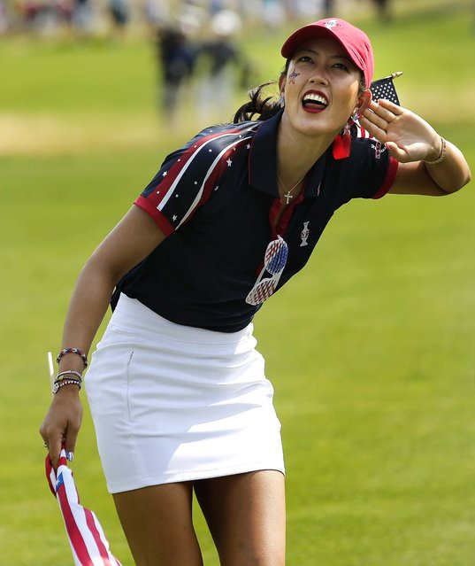 Michelle Wie encourages the crowd along the 15th fairway during a foursome match in the Solheim Cup golf tournament in Parker, Colorado, on August 16, 2013. (Photo by Chris Carlson/Associated Press)
