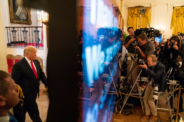 """US President Donald J. Trump (L) enters an event to honor federal immigration agents in the East Room of the White House in Washington, DC, USA, 20 August 2018. The event, which the White House is calling a """"Salute to the Heroes of the Immigration and Customs Enforcement and Customs and Border Protection"""", comes after the administration's """"zero-tolerance"""" policy caused hundreds of migrant children to be separated from their parents. (Photo by Jim Lo Scalzo/EPA/EFE)"""