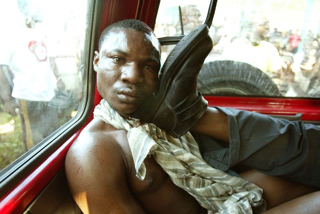 A Haitian suspected of being a multiple assassin for exiled president Jean Bertrand Aristide's Lavalas party is detained in Petit Goave, in this March 3, 2004 file photo. The man was detained by armed citizens of Petit Goave who proceeded to stone him and then burn him alive. (Photo by Daniel Aguilar/Reuters)