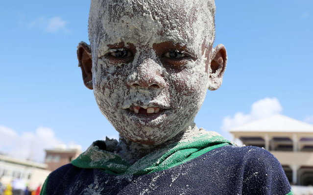 A Somali boy covers his face with sand at the Liido Beach during the last Friday ahead of the Muslim holy month of Ramadan, amid the coronavirus disease (COVID-19) pandemic in Mogadishu, Somalia on April 9, 2021. (Photo by Feisal Omar/Reuters)