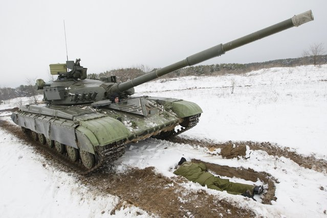 "An instructor riding on a tank and a newly mobilized soldier take part in training at the 169th training center of Ukrainian ground forces ""Desna"" in the Chernihiv region February 13, 2015. (Photo by Valentyn Ogirenko/Reuters)"