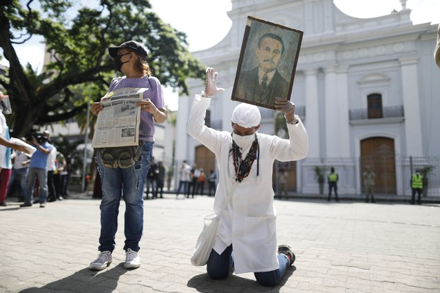 "Yeni Vasquez raises a portrait of the late, Venezuelan Dr. Jose Gregorio Hernandez outside the church in La Candelaria after the church bell rang, signaling the start of his Beatification ceremony in Caracas, Venezuela, Friday, April 30, 2021. Known as the ""doctor of the poor"", Hernandez is being Beatified by the Catholic church, a step towards sainthood. (Photo by Ariana Cubillos/AP Photo)"