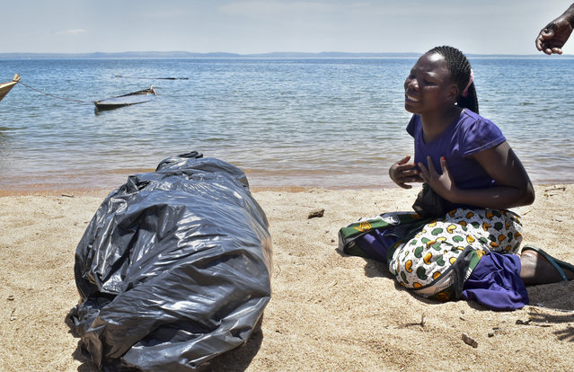 A woman cries beside the body of her sister, a victim of the MV Nyerere passenger ferry, as she awaits transportation for burial on Ukara Island, Tanzania Saturday, September 22, 2018. The death toll soared past 200 on Saturday while officials said a survivor was found inside the capsized ferry and search efforts were ending to focus on identifying bodies, two days after the Lake Victoria disaster. (Photo by Andrew Kasuku/AP Photo)