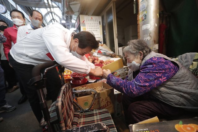 Oh Se-hoon, left, the candidate of the main opposition People Power Party, bumps fists with a vendor during a campaign for the April 7 Seoul mayoral by-election at a market in Seoul, South Korea, Tuesday, April 6, 2021. (Photo by Ahn Young-joon/AP Photo)