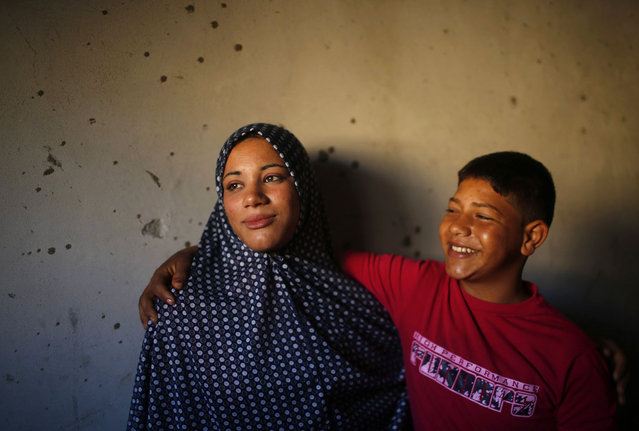 Newly married Tala Soboh, 14, poses for a photograph with her 15-year-old husband Ahmed two days after their marriage in the town of Beit Lahiya, near the border between Israel and the northern Gaza Strip September 26, 2013. The newlyweds live in the family's three-room home, sharing it with nine relatives. Ahmed works with his father as a road cleaner earning $5 per day. (Photo by Mohammed Salem/Reuters)