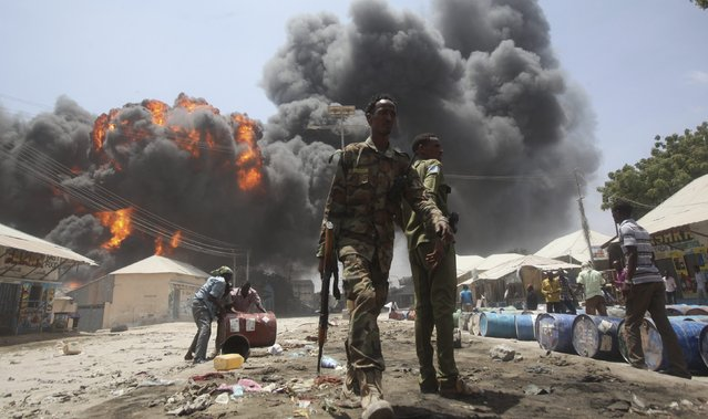 Soldiers watch as people move oil barrels away from the site of an explosion at a petrol station and storage facility near the Bakara open-air market in Somalia's capital Mogadishu, February 23, 2015. (Photo by Ismail Taxta/Reuters)