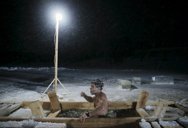 A man immerses himself in icy waters during celebrations for the Orthodox Epiphany on the ice-covered lake near the village of Dubrovichi outside Ryazan, Russia, January 19, 2016. Orthodox believers mark Epiphany on January 19 by immersing themselves in icy waters regardless of the weather. (Photo by Maxim Shemetov/Reuters)