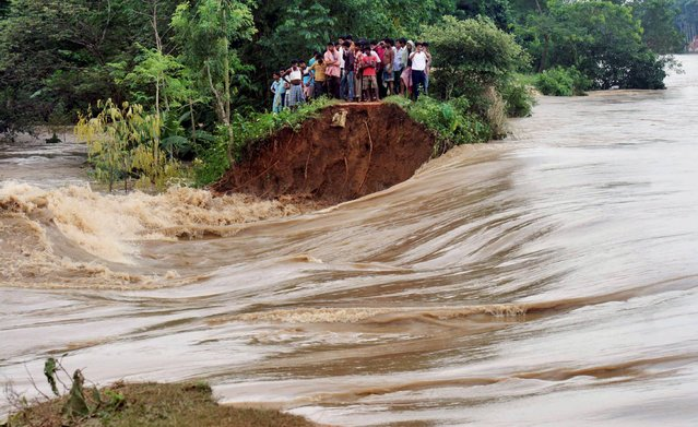 Indian villagers stand on the breached embankment of swollen Kangsabati river at Samat village in West Bengal state, India, Tuesday, October 15, 2013. Heavy torrential rain in the aftermath of weekend Cyclone Phailin have made rivers to overflow causing flood situation in the state. (Photo by AP Photo)
