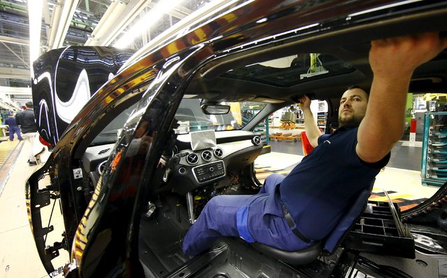 An employee of German car manufacturer Mercedes Benz works on the interior of a GLA model at their production line at the factory in Rastatt, Germany, January 22, 2016. (Photo by Kai Pfaffenbach/Reuters)