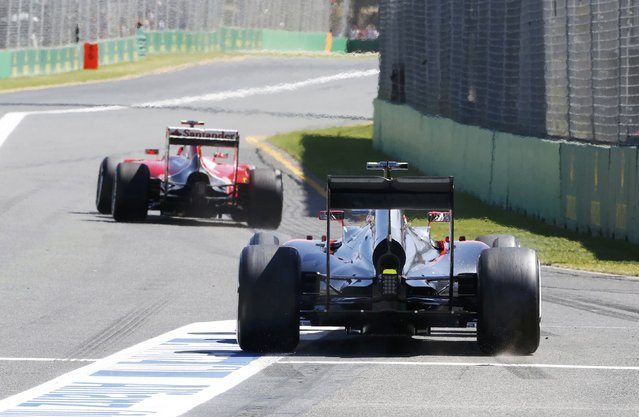 Ferrari Formula One driver Kimi Raikkonen of Finland (front) and McLaren driver Jenson Button of Britain leave the pit lane during the first practice session of the Australian F1 Grand Prix at the Albert Park circuit in Melbourne March 13, 2015. REUTERS/Brandon Malone