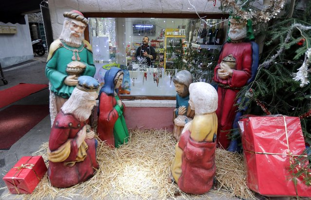 A Nativity scene is seen next to a grocery store in the medieval mountain village of Luceram as part of Christmas holiday season, France, December 15, 2016. (Photo by Eric Gaillard/Reuters)