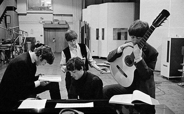 """The Beatles in EMI Recording Studios (later renamed Abbey Road Studios), London, England, 1964, by David Hurn. """"In 1964, I was asked by my friend Richard Lester, who was about to direct the first Beatles film A Hard Day's Night, to photograph it, not for press, but more from a sociological point of view. My picture shows the four of them studying pages of the script for the following day's shooting. They are in the Abbey Road Studio, the scene of so many of their musical triumphs"""". (Photo by David Hurn/Magnum Photos)"""