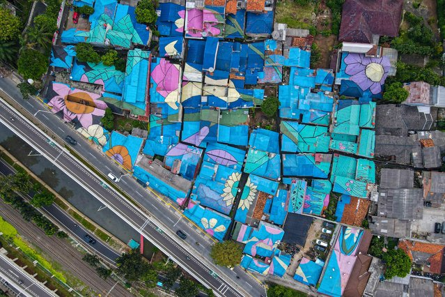 This aerial photo shows residents' homes painted by the local government in Jakarta on June 2, 2021. (Photo by Bay Ismoyo/AFP Photo)