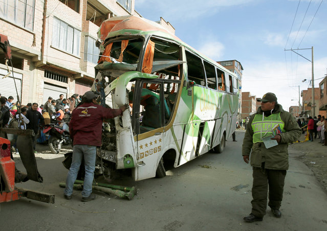 A policeman walks next to wreckage of a bus that crashed into a semi-trailer, which resulted in multiple fatalities in Calajahuira outskirts of La Paz, Bolivia, December 23, 2016. (Photo by David Mercado/Reuters)