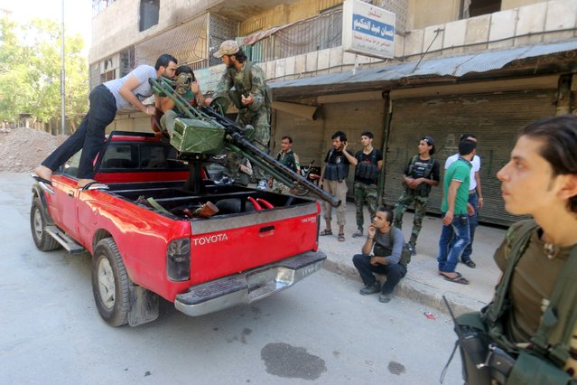 Free Syrian Army fighters inspect a pick-up truck with a weapon installed on it as they carry their weapons while they gather in what they said was an operation to travel to the northern countryside of Aleppo to fight Islamic State fighters in Aleppo, Syria, September 3, 2015. (Photo by Abdalrhman Ismail/Reuters)