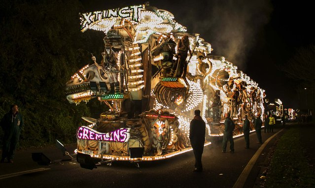 The Gremlins Carnival Club's illuminated cart, Xtinct, waits to take part in the Glastonbury Carnival in Glastonbury, England, on November 16, 2013. The carnival is one of a series of parades, in towns throughout Somerset in November, widely regarded as among the largest illuminated processions in the world. The major regional event dates back to the Gunpowder Plot of 1605. (Photo by Matt Cardy/Getty Images)
